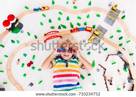 Kids play with toy train railway. Child playing with wooden trains. Toys for little boy. Preschooler building rail road and blocks at home or daycare, preschool. Kindergarten educational games. #710234752