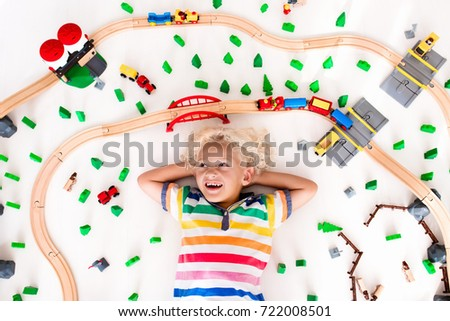 Kids play with toy train railway. Child playing with wooden trains. Toys for little boy. Preschooler building rail road and blocks at home or daycare, preschool. Kindergarten educational games. #722008501