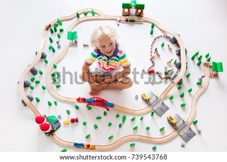 Kids play with toy train railway. Child playing with wooden trains. Toys for little boy. Preschooler building rail road and blocks at home or daycare, preschool. Kindergarten educational games. #739543768