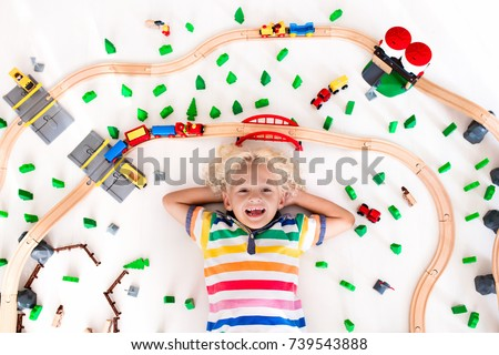 Kids play with toy train railway. Child playing with wooden trains. Toys for little boy. Preschooler building rail road and blocks at home or daycare, preschool. Kindergarten educational games. #739543888