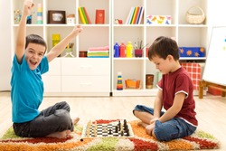 Kids playing chess - one of them just captured a pawn and celebrates