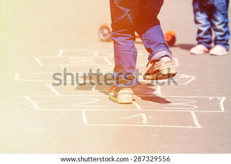 Shutterstock kids playing hopscotch on playground outdoors, children outdoor activities
