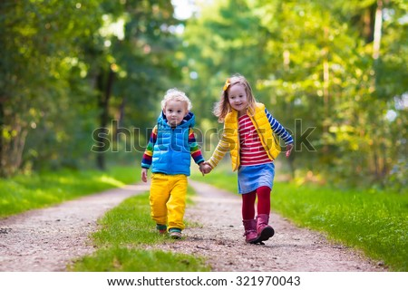 Kids playing in autumn park. Children play outdoors on a sunny fall day. Boy and girl running together hand in hand in a forest. Toddler and preschooler pick colorful oak leaf. Family fun outdoor #321970043