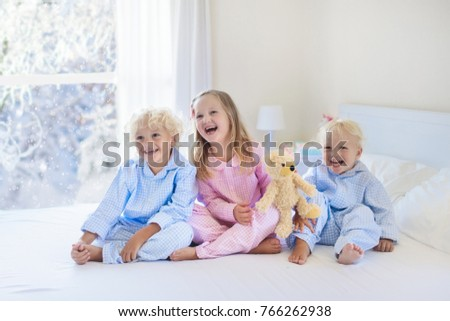 Kids playing in parents bed in winter. Children wake up in white bedroom by snow. Little kid in pajamas. Christmas sleepwear and bedding for child and baby. Family morning on snowy cold Xmas day.