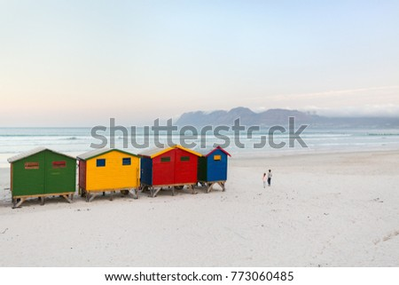 Kids playing near famous colorful huts of Muizenberg beach near Cape Town in South Africa