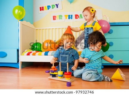 Kids playing on birthday party constructing a pyramid and girl putting on celebration caps