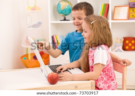 Kids playing on laptop computer at home together