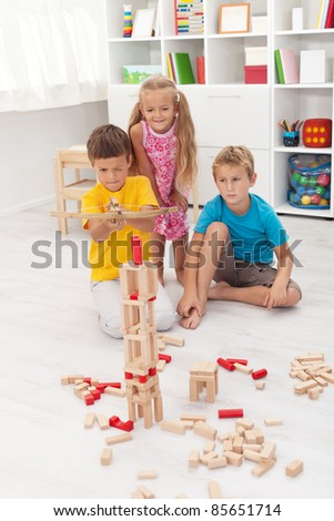 Kids playing with a bow and arrow - shooting a wooden blocks tower
