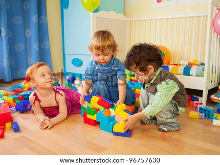 Kids playing with plastic blocks - two boys and girl - stock photo