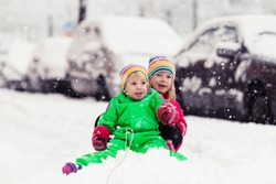 kids playing with snow slider. preschoolers building snowman outside. winter adventure for children. siblings in bright warm overalls. girl and boy sitting in snow buggy.