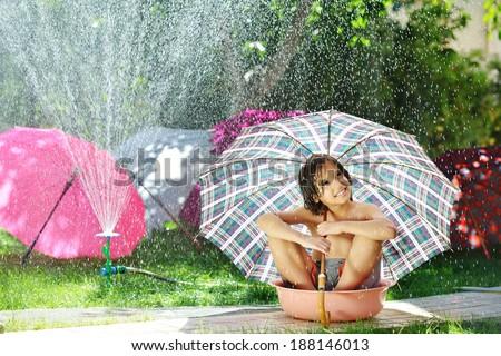 Kids playing with sprinkler water holding umbrella on summer backyard