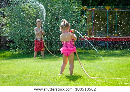 Kids playing with water on a warm summerday in the garden