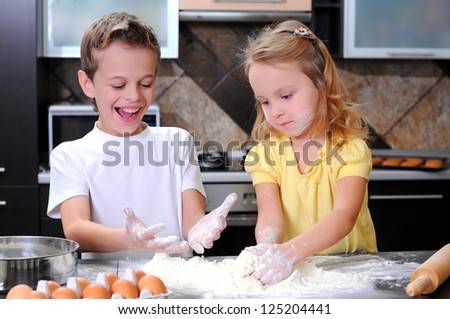 Kids preparing the dough for a cookie, pizza or pasta - having fun breaking the eggs