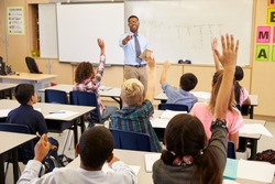 Kids raising hands to answer in an elementary school class