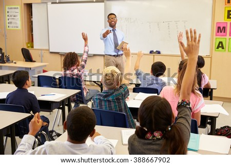 kids raising hands to answer in ...