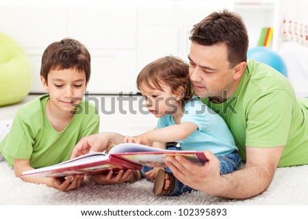 Kids reading story book with their father - sitting on the floor