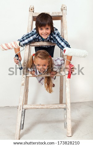 Kids ready to paint the wall - climbing a ladder holding paint roller