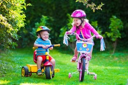 Kids riding bikes in a park. Children enjoy bike ride in the garden. Girl on a bicycle and little boy on a tricycle in safety helmet playing together outdoors. Preschool child and toddler kid biking.