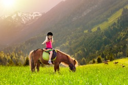 Kids riding pony in the Alps mountains. Family spring vacation on horse ranch in Austria, Tirol. Children ride horses. Kid taking care of animal. Child and pet. Little girl in blooming meadow.