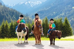 Kids riding pony in the Alps mountains. Family spring vacation on horse ranch in Austria, Tirol. Children ride horses. Kid taking care of animal. Child and pet. Little girl and boy in saddle on pony.