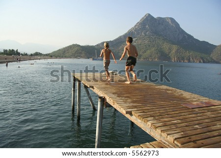 kids running and jumping from pier