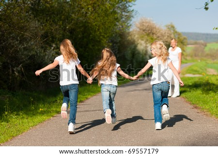 kids running down a path in spring, their mother standing in the background