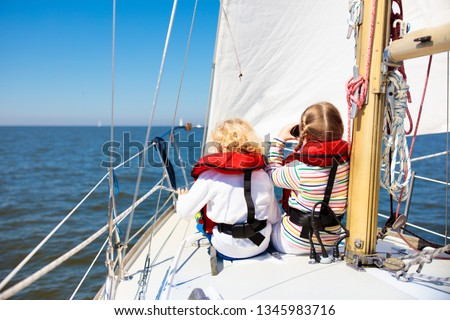 Kids sail on yacht in sea. Child sailing on boat. Little boy and girl in safe life jackets travel on ocean ship. Children enjoy yachting cruise. Summer vacation for family. Young sailors on sailboat. #1345983716