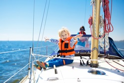 Kids sail on yacht in sea. Child sailing on boat. Little boy in safe life jacket travel on ocean ship. Children enjoy yachting cruise. Summer vacation for family. Young sailor on sailboat front deck.