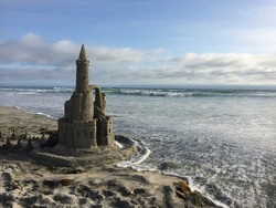 Kids sand castle moat protects against ocean waves on a sunny beach with blue skies during vacation