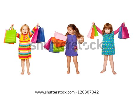 Kids shopping. Group of happy little fashion girls with shopping bags. Isolated on white background