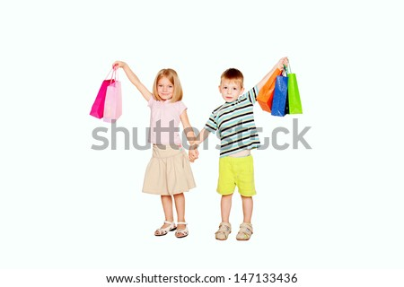 Kids shopping. Young couple, a little boy and a little girl, holding up shopping bags, ready for your text, logo or symbols.. Isolated on white background.