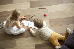 Kids sister and brother playing drawing together on wooden warm floor in living room, creative children boy and girl having fun at home, siblings friendship, underfloor heating concept, top view