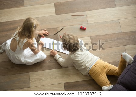 Kids sister and brother playing drawing together on wooden warm floor in living room, creative children boy and girl having fun at home, siblings friendship, underfloor heating concept, top view #1053737912