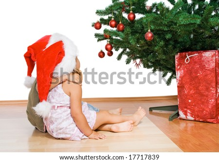 Kids sitting in front of the christmas tree hugging - isolated
