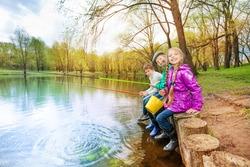 Kids sitting near pond holding fishing tackles