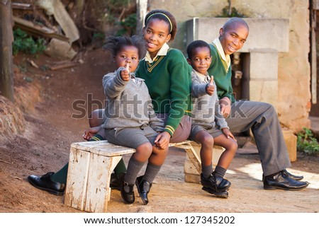 Kids sitting on a bench waiting for the school bus. - stock photo