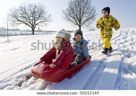 Kids sliding in the snow.