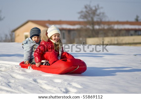 Kids sliding in the snow.