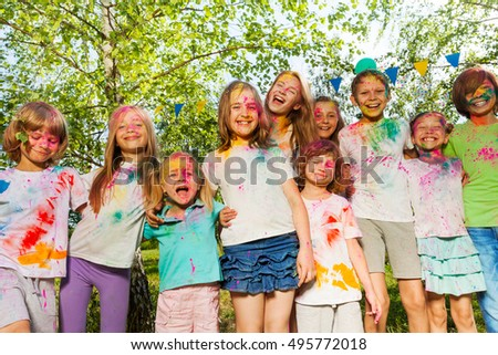 Kids smeared with colored powder standing in a row #495772018