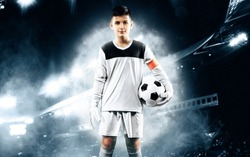 Kids - soccer champion. Boy goalkeeper in football sportswear on stadium with ball. Sport concept.