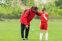 Kids soccer football - coach comfort little soccer player who is crying after a missed goal