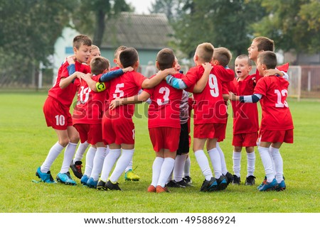 kids soccer team in group huddle