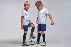 kids soccer team on training, two boys practicing game with a soccer ball in studio. training football session for children on soccer camp. young boy improving dribbling skills