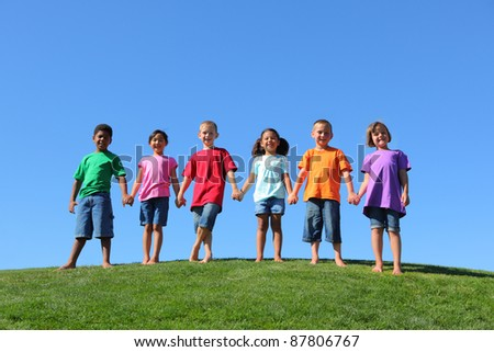 Kids standing on grass hill with blue sky