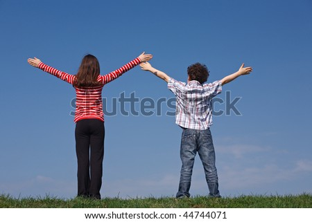 Kids standing with open arms against the blue sky
