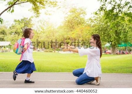 Kids student running into mother\'s hands to hug her after back to school.