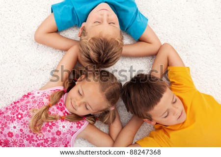 Kids taking a break relaxing on the floor with eyes closed