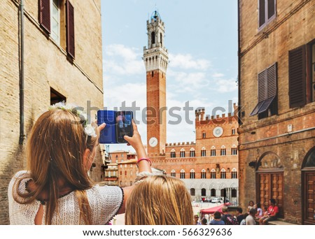 Shutterstock Kids taking picture with the smartphone of Piazza del Campo, Siena, Italy