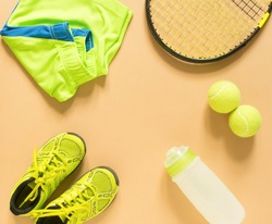Kids tennis stuff on cream background. Sport, fitness, tennis, healthy lifestyle, sport stuff. Tennis racket, lime trainers, tennis ball, lime athletic shorts, sports bottle. Flat lay, top view.