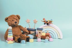 Kids toys collection. Teddy bear, wooden rainbow, train and baby toys on light blue background